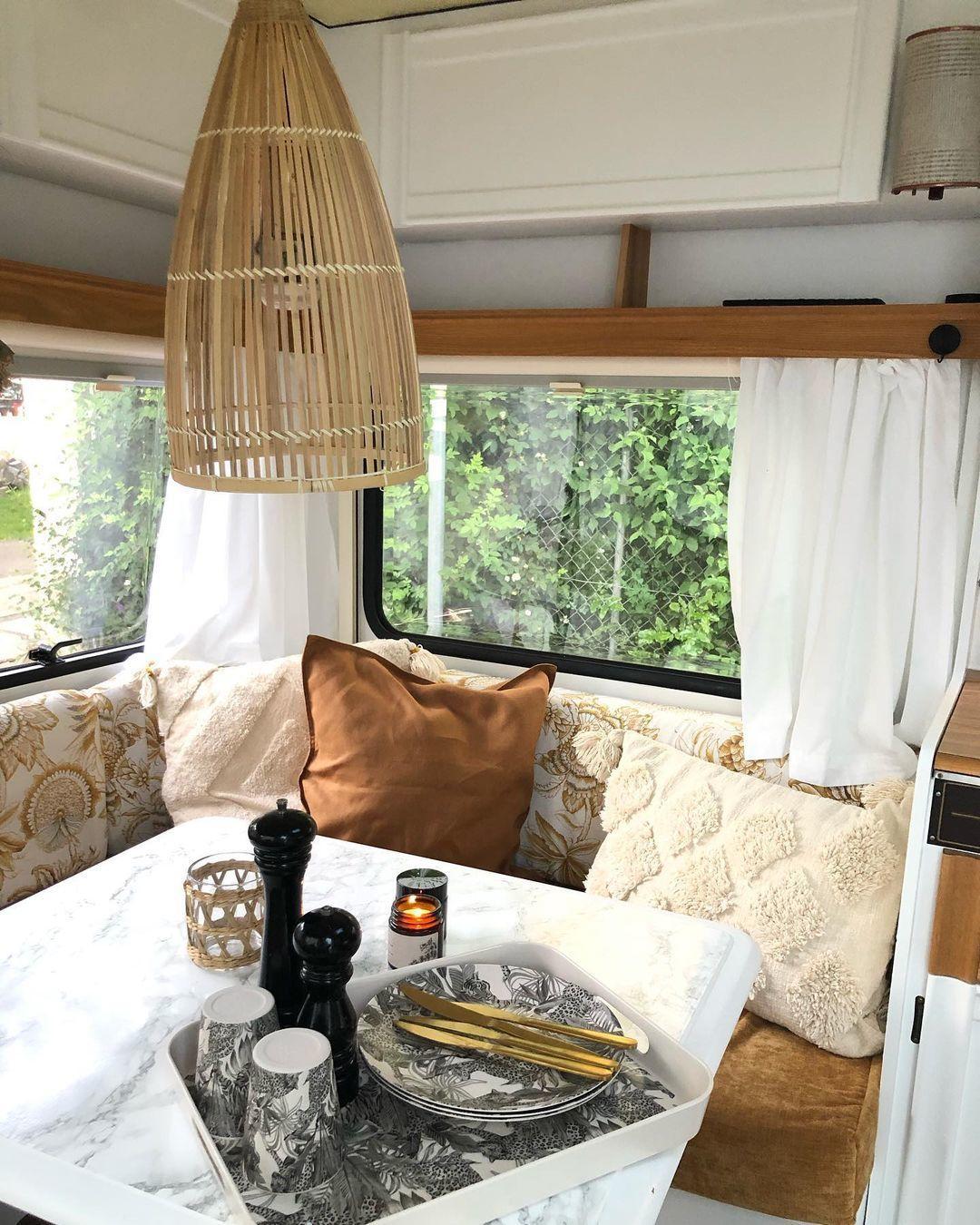 Blick durch das Frontfenster in den hell frisch renovovierten Wohnwagen in Erdtönen - Caravan Service Stehmeier