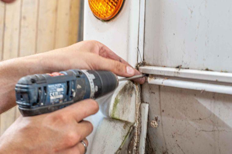 Caravan Reparatur an der Heckschürze eines Wohnwagens Schrauben befestigen - Caravan Service Stehmeier
