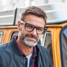 Profilbild Inhaber Marcus Stehmeier vor einem orangen VW T1 Bus - Caravan Service Stehmeier - Wohnmobil Wohnwagen Service Werkstatt
